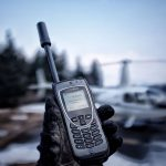 Iridium Satellite Phone with Helicopter blurred in background